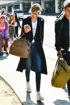 Gigi's high-waisted jeans elongate her legs, and a fitted top keeps things simple but sexy. Her calf-length coat stretches her silhouette even more and smartly doubles as a perfect blanket or pillow after you've found your seat on the plane. Go-to pieces: High-waisted skinnies, fitted top, long cardigan.