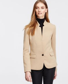 """Meticulously designed in doubleweave fabric, this polished piece flatters with clean lines, noteworthy neutrals and beautifully tailored fit. Notched stand collar. Long sleeves with functional sleeve buttons for added styling options. One button front. Front flap besom pockets. Back vent. Lined. 25"""" long."""