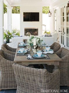 fireplace w/ tv, white slipcovered seating, wicker dining chairs all make for a…
