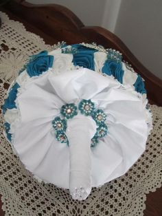 Teal and white wedding bouquet with white satin gathered wrap and vintage beaded buttons as and edging around stem.