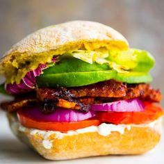 This sticky-sweet BBQ tempeh sandwich is easy to whip up! Fresh tomato, avocado, and onion to accent.