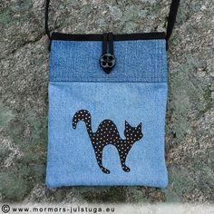 Ett återbruk. Handtryckt mönster på jeanstyg. Katten är svart med guldfärgade prickar.  Liten praktisk axelremsväska för mobil, kort mm. På baksidan finns en liten ficka, se bild. Tyg av återvunna jeans och bomullstyg i fodret.  Storlek 18,5 x 23 cm. Axelrem 111 cm.