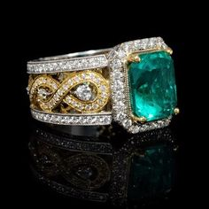 This magnificent 18k white and yellow gold antique style ring features 170 round brilliant cut white diamonds, weighing 1.11 carats total with 1 GIA Certified Colombian emerald, weighing 3.66 carats total.