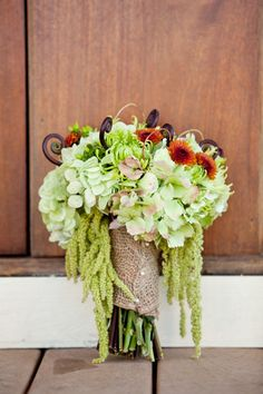 Gorgeous and unique late summer or autumn / fall wedding bouquet - green hydrangea, Fuji mums,  hpericum, rust colored chrysanthemums, hanging amaranthus, and fiddle-head fern wrapped with burlap and embellished with pearl pins.