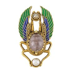 Egyptian Revival Gold, Amethyst Scarab, Enamel, Pearl and Diamond Pin -  The stylized beetle centering one oval amethyst scarab approximately 13.35 x 11.05 mm., tipped by one pearl approximately 5.15 mm., and one old-mine cut diamond, its wings applied with green and blue enamel, circa 1870, approximately 8.3 dwts.