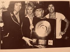 Queen giving a golden disc to Groucho Marx [circa Groucho Marx, Queen Freddie Mercury, Brian May, John Deacon, Queen Drummer, Sorry My Love, Princes Of The Universe, Tiger Skin, Blues