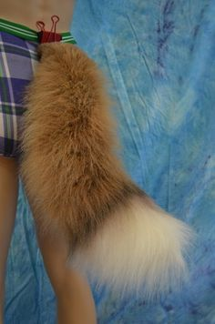 A fox tail made from from high-quality, realistic, fake furs (not real fur) in TAN with black airbrushing.  - approximately 24 inches long.  - 2 elastic beltloops. The robust elastic can stretch to fi