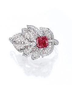EXQUISITE AND VERY RARE FANCY RED DIAMOND AND DIAMOND RING.  Centring on a rectangular modified brilliant-cut fancy red diamond weighing 1.92 carats, nestled within a leaf set with brilliant-cut diamonds together weighing approximately 2.00 carats, mounted in platinum.