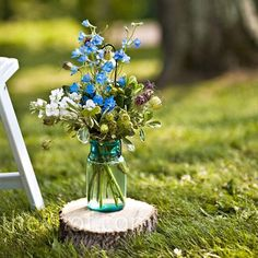 with nigella, blue delphinium, and white stock sat on cross sections of tree trunks lining the ceremony aisle.