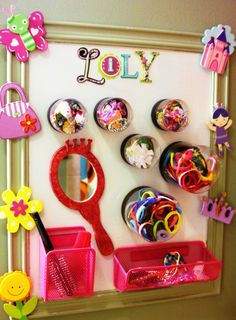 """Organizational Board for Lily's Hair Accessories:  Magnetic """"calendar"""" white board painted white, clear plastic jars (paint dept) with magnets hot glued to the lids, """"locker baskets"""" for brushes, etc., wooden mirror painted and hot glued to the board, wooden cutouts hot-glued to frame.  Now finally, a cute and cohesive place for hair bands, barrettes, pony tail holders, you name it!"""