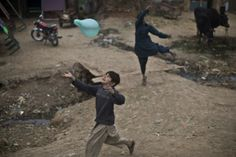 An Afghan refugee chases a balloon while playing in a poor neighborhood on the outskirts of Islamabad, Pakistan, on Feb. 2.