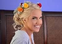 A Bridal updo with brightly colored roses and babies breath.