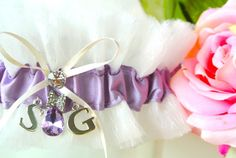 This is a custom design I made for La Gartier bride Kelly Loos in December of 2012. Kelly wanted a lilac purple wedding garter with a hanging Amethyst colored pendant. In addition, she wanted to have the initials S & G to personalize the garter and make it her own.