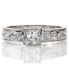 Antique inspired, beautiful, unique diamond solitaire engagement ring. The beautiful hand engraving swirls out and away from the bezel set center stone. Princess cut, bezel set center stone and a hand engraved band. Juno from Knox Jewelers