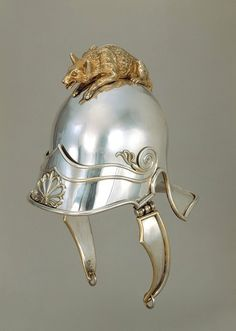 Helmet. 1811-12, London, England. This helmet fashioned from silver and gilt is an extravagant piece. This type of helmet was introduced for cavalry soldiers in the Napoleonic wars. A wolf, a symbol of ferocity, sits on top of the helmet.