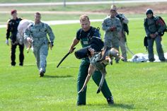 Military working dog, Sgt. Maj. Fosco, flies through the air at an aggressor wearing protective gear during a K-9 demonstration after landing safely onto Gammon Parade Field, and making history with the military's first tandem airborne jump from an altitude of 12,500 feet during Military Police Warfighter Week, Fort Leonard Wood, Mo., Sept. 18, 2009. Lalonde is assigned to Company D, 701st Military Police Battalion. U.S. Army photo by Ben Morrow