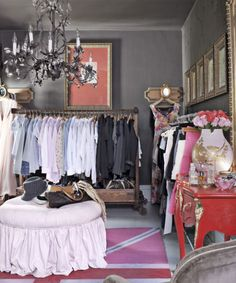 Old Rule: Have a guest room double as an office or den. New Rule: Turn the room into a single indulgence, like a walk-in closet.  The house's second bedroom is used as a dressing area. Carney covered the ottoman in pink denim from Walmart and spray-painted an outdoor rug.