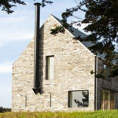 Mortehoe House is a gabled family retreat by McLean Quinlan Architects on the Devon coastline in England with walls of weathered stone and timber..