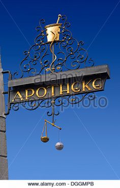 Historical Apotheke sign, German for pharmacy, with a mortar and pestle and hand scales at a pharmacy in Konstanz - Stock Photo