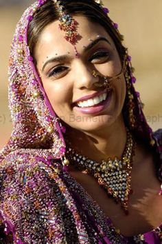An Indian bride dressed in a traditional Punjabi suit (salwar kameez) in a vibrant purple color with heavy work on the dupatta.