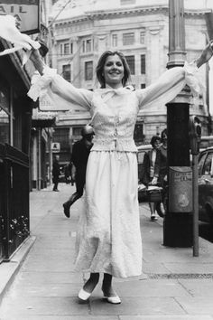 A woman shows off her Christian Dior wedding gown on the street in London, 1970
