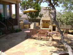 Perfect for summer holidays! Beautiful Stone Outdoor Kitchen & Fireplace Area by DH Landscape.