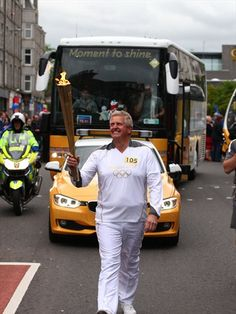 Golfer Colin Montgomerie carries the Olympic Flame between Cults and Aberdeen during Day 24 of the Olympic Torch Relay