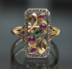 Art Nouveau Ring: Gold Platinum Emerald Ruby Diamond. Head of Bacchus & owl mark, French, c.1910 / http://www.tademagallery.com/content.htm