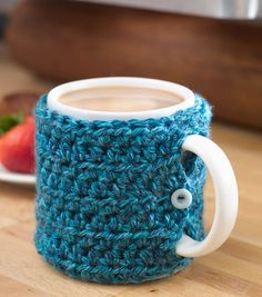 "One Stitch Mug Cozy Chain 32. Row 1: Half double crochet in 3rd chain fr hook and in each chain across. Row 2: Chain 2, turn. Half double crochet in each stitch across - 29 st Repeat Row 2 until piece measures about 9-1/2"", when slightly stretched. Fasten off. Sew short sides of Cozy together for about 1/2"" at top and at bottom, leaving remaining 2-1/2""open for mug handle. sew button, centered"