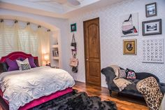 Gray and white patterned walls set a stylish backdrop for this teen girl's bedroom. A hot pink upholstered bed is glamorous and girly, and a charcoal gray chaise is charming and luxurious.
