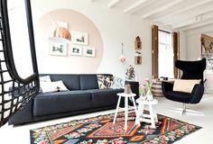 salon noir et blanc avec peinture murale blanche à motif cercle beige clair, canapé gris anthracite, fauteuil noir, tables d'appoint blanches et tapis bariolé