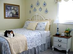 This cat-approved guest bedroom submitted by RMS user susiehomemaker is filled with shabby chic finds from consignment stores and the Internet. The cottage-style bedroom incorporates blue and white floral linens and a charming gallery wall of plates.