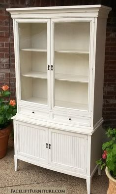 China Cabinet in distressed Off White with Tobacco Glaze. Single wide drawer, and lower storage with shelf. Original pulls painted dark bronze.From Facelift Furniture's Hutches, Cabinet & Buffet's Collection.