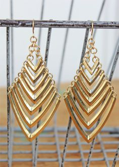 """Don't do dull. Stand out with this dramatic statement earring formed from gold chevron layers. Hook earring. Measures 3"""" in length including hook and 1.5"""" in width.  $20.00"""
