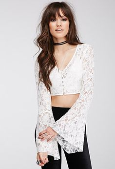 Taking it back to the '70s with its floral lace fabrication and long bell sleeves, this crop top was made for festival days then, now, and on. Complete with a pearlescent button-down front, it's the perfect semi-sheer topper to dance under the desert sun.