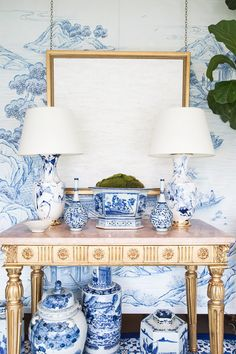 Blue and white porcelain styled on table with mimicking wallpaper in the background