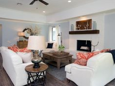 Fixer Upper's Chip and Joanna Gaines added new wood flooring to replace the blue, outdated wall-to-wall carpeting in this renovated living room. The brick fireplace was painted bright white, a new mantel was installed and the fireplace doors were removed for a more modern look.