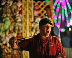"""Robert Alonzo of Boston tries to lure fair goers to try the """"Hi Striker"""" test of skill. Players use the large hammer to try and ring the bell. His mom and dad worked carnivals when he was a child, he has followed them by working Fiesta Show games for thirteen years. Greg Derr/The Patriot Ledger"""