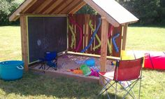 Covered kids entertainment area with sandbox, chalkboard and colorful ball tubes.
