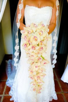 Draping is not only seen in apparel but can be used in floral decor as well. You can see in this picture the bride holding her bouquet.  The flowers are draping which has been pretty popular this wedding season.