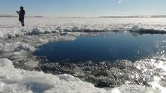 A handout photo taken on February 15, 2013, and provided by Chelyabinsk region police department shows a police officer standing near a six-metre (20-foot) hole in the ice of a frozen lake, reportedly the site of a meteor fall, outside the town of Chebakul in the Chelyabinsk region. Divers scoured today  the bottom of a Russian lake for fragments of a meteorite that plunged to Earth in a blinding fireball whose shockwave injured 1,200 people and damaged thousands of homes. AFP PHOTO…