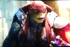 Raphael looking at his brothers while holding the small vial of retro-mutagen, thinking about his decision on what he's going to make.