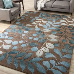 Add an elegant new style to a room with this 100 percent polyester hand-tufted rug. The lush blue floral patterns adorn a brown background, creating a soft blend of natural colors. Peacock, sky, pastel blue, and teal bring dimension and beauty.