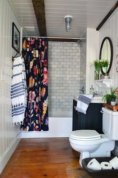 Old farmhouse bathroom renovation with salvaged wide pine floors. Marble subway tile surround is accented with a bright Anthropologie shower curtain. A dark painted vanity base supports a vintage cast iron sink. Turkish bath towels, vintage mirror, buffalo art, and vintage first aid kits accessorize the space.