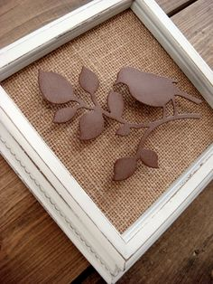 White distressed frame with a metal 3-dimensional bird on a tree limb on a burlap background.
