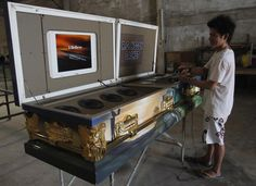 A worker selects a song on a coffin equipped with a karaoke system while taking a break at a casket manufacturing factory in Pampanga province, north of Manila, Philippines October 30, 2012. Coffin manufacturer Robert Nogoy replaces the insides of a casket with a karaoke machine as a gimmick to surprise guests and lighten the mood of solemn funerals or Halloween parties. REUTERS/Cheryl Ravelo