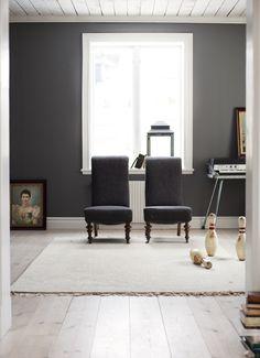 Rummet är målat i en mörkgrå färg med härlig tyngd, pigeon grey, ur Li Edelkoorts kollektion för Alcro. Två svanhalsfåtöljer är blickfång i rummet, bowlingkäglor från USA och matta från Ikea.