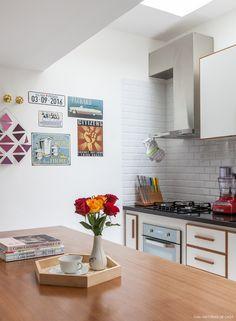 Cozinha de casa de vila tem ilha central, revestimentos de azulejos subway e marcenaria com puxadores de madeira.