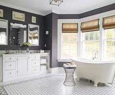 Don't be afraid of dark bathroom walls. Deep hues can create a sense of comfort and element of drama. Charcoal, which is warmer than other grays but not as harsh as black, combines with white in this serene space for understated elegance. Royal green accents found in the curtain trim and wall art rev up the combo.