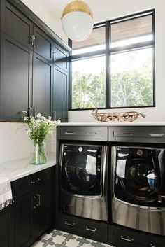 Hicks Pendant decorates a black and white laundry room with an antique brass finish above stainless steel front load washer and dryer with black pedestals. White Laundry Rooms, Small Laundry, Black Appliances, Home Appliances, Decoracion Vintage Chic, Modern Lake House, Laundry Room Inspiration, Studio Mcgee, Bonus Rooms